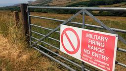Tanda dari Menteri Pertahanan Inggris yang memperingatkan pengunjung bahwa mereka berada di jarak tembak dekat Dorset, Inggris, 8 Juli 2018. Tyneham berada di tangan militer sejak 1943 hingga saat ini. (AP Photo/Jerry Harmer)