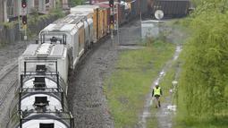 Kondisi kereta barang CSX yang keluar dari rel di bagian timur laut Washington, Minggu (1/5). Menurut keterangan, setidaknya sembilan gerbong kereta anjlok dengan tiga gerbong di antaranya menumpahkan zat kimia berbahaya ke rel. (Andrew BIRAJ /AFP)