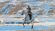 Pemimpin Korea Utara Kim Jong-un menunggangi kuda putih  saat salju yang turun di gunung Paektu (16/10/2019). Kim Jong-un tampil mengenakan kaca mata dengan mantel tebal berwarna coklat.  (Photo by STR/KCNA VIA KNS/AFP)