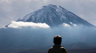 Seorang turis melihat Gunung Fuji dari Fujikawaguchiko, Prefektur Yamanashi, Jepang (1/11). Gunung Fuji adalah gunung tertinggi di Jepang, terletak di perbatasan Prefektur Shizuoka dan Yamanashi, di sebelah barat Tokyo. (AFP Photo/Behrouz Mehri)