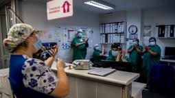 Perawat Chile, Damaris Silva memainkan biola untuk pasien COVID-19 di Unit Perawatan Intensif rumah sakit El Pino di Santiago pada 9 Juli 2020. Silva melakukan ini untuk memberikan cinta, keyakinan, harapan dan semangat kepada pasien dan perawat yang sedang bertugas. (Martin BERNETTI / AFP)