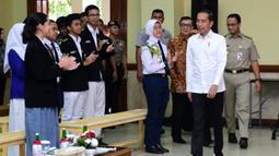 Presiden Joko Widodo (kemeja putih) tiba untuk menyaksikan drama bertajuk Prestasi Tanpa Korupsi di SMKN 57 Jakarta, Jakarta Selatan, Senin (9/12/2019). Kegiatan tersebut dalam rangka memperingati Hari Antikorupsi Sedunia. (Liputan6.com/Biropres Kepresidenan)