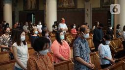 Umat Katolik melaksanakan ibadah misa dengan tetap mengenakan masker di Gereja Katedral Jakarta, Minggu (12/7/2020). Gereja Katedral Jakarta kembali menggelar misa bagi umat Katolik dengan menerapkan protokol kesehatan untuk mencegah penularan Covid-19. (Liputan6.com/Immanuel Antonius)