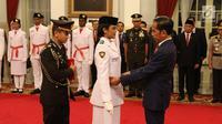 Presiden Joko Widodo (kanan) memasangkan kendit kepada perwakilan anggota Pasukan Pengibar Bendera Pusaka (Paskibraka) saat pengukuhan di Istana Negara, Jakarta, Kamis (15/8/2019). Sebanyak 68 anggota Paskibraka tersebut akan bertugas pada upacara HUT ke-74 RI. (Liputan6.com/Angga Yuniar)