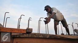 Pekerja menyelesaikan proyek pembangunan tanggul di Pantai Muara Baru, Jakarta, Rabu (2/12). Proyek pembangunan tanggul tersebut bertujuan untuk menahan banjir rob yang sering melanda kawasan Muara Baru. (Liputan6.com/Gempur M Surya)