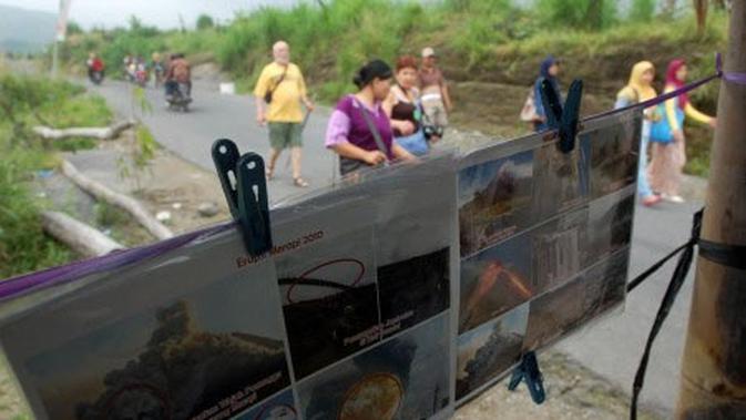 Sejumlah wisatawan melintas di dekat salah satu tempat penjual foto kejadian erupsi merapi Oktober 2010 di kawasan Gunung Merapi, Kinahrejo, Umbulharjo, Cangkringan, Yogyakarta. (Antara)