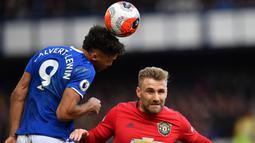 Bek Manchester United, Luke Shaw, duel udara dengan striker Everton, Dominic Calvert-Lewin, pada laga Premier League di Stadion Goodison Park, Minggu (1/3/2020). Kedua tim bermain imbang 1-1. (AFP/Paul Ellis)