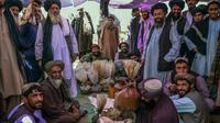 Penjual opium dan pembeli mengobrol tentang teh hijau di sekitar karung opium dan hashish di sebuah pasar opium di Kandahar, Afghanistan (BULENT KILIC / AFP)
