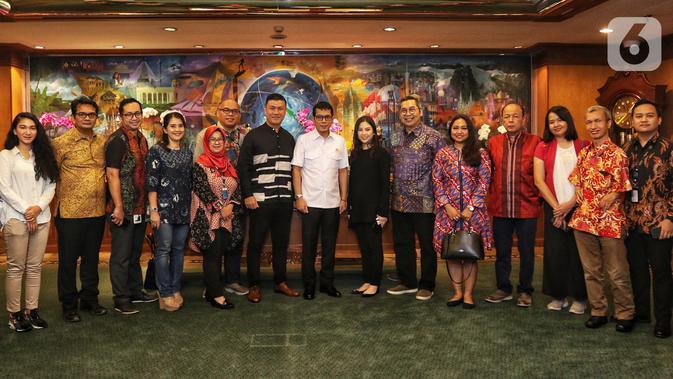 Menteri Pariwisata dan Ekonomi Kreatif Wishnutama (tengah) dan Wakil Menteri Angela Tanoesoedibjo (ketujuh kanan) foto bersama jajaran Emtek dan SCM Group saat menerima kunjungan di Kantor Kemenpar, Jakarta, Jumat (8/11/2019). Pertemuan membahas kerja sama sektor media. (Liputan6.com/JohanTallo)