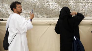 Seorang jemaah haji mengabadikan istrinya saat melempar batu melaksanakan lempar jumrah di Mina, dekat kota suci Makkah, Arab Saudi (11/8/2019). Usai wukuf di Padang Arafah, jutaan jemaah haji melanjutkan lempar jumrah yang merupakan simbol perlawanan terhadap setan. (AP Photo/Amr Nabil)