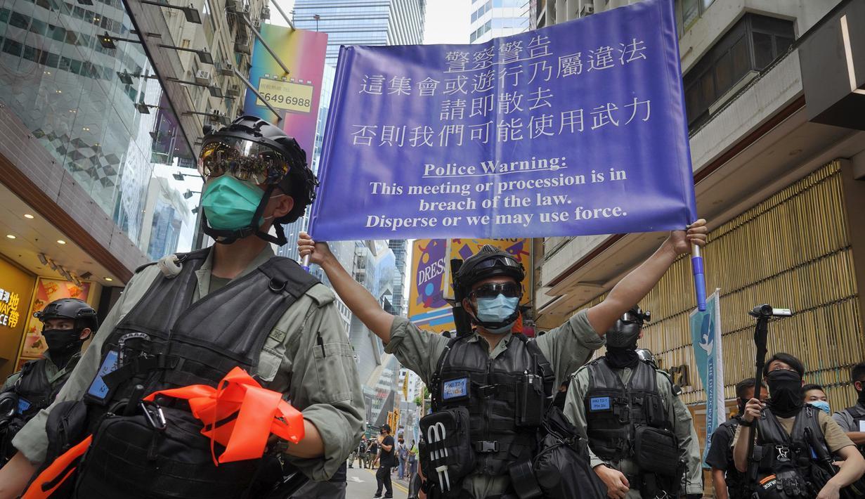 Polisi memajang spanduk peringatan kepada pengunjuk rasa yang menentang Undang-Undang Keamanan Nasional di Causeway Bay sebelum pawai penyerahan tahunan di Hong Kong, Rabu (1/7/2020). Hong Kong menandai peringatan 23 tahun penyerahannya ke China pada tahun 1997. (AP Photo/Vincent Yu)
