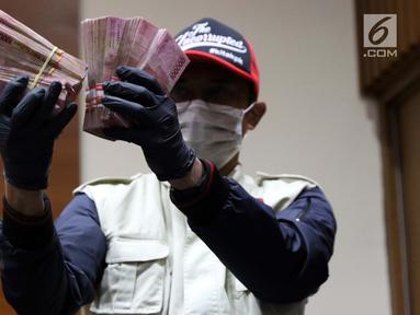 Petugas KPK menunjukkan barang bukti hasil Operasi Tangkap Tangan (OTT) terkait pengisian jabatan perangkat daerah di lingkungan Pemkab Kudus, Gedung KPK Jakarta, Sabtu (27/7/2019). KPK menetapkan tiga tersangka, salah satu diantaranya Bupati Kudus, M Tamzil. (Liputan6.com/Helmi Fithriansyah)