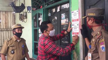 Petugas memasang stiker tempat warga isolasi mandiri