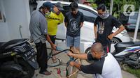 Warga bersiap melakukan penyemprotan cairan disinfektan di perumahan Cinere Green Valley, Tangerang Selatan, Banten, Kamis (26/3/2020). Penyemprotan disinfektan secara mandiri ini dilakukan untuk mengantisipasi penyebaran virus corona COVID-19 di lingkungan mereka. (Liputan6.com/Faizal Fanani)