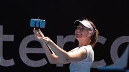 Ekspresi Maria Sharapova saat berselfie dengan penggemarnya usai pertandingan melawan Tatjana Maria pada putaran pertama di kejuaraan tenis Australia Terbuka 2018 di Melbourne (16/1). Sharapova menang 6-1, 6-4. (AP Photo / Vincent Thian)