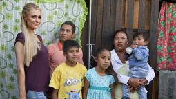 Paris Hilton foto bersama dengan salah satu keluarga terkena dampak gempa bumi pada September 2017 di San Gregorio Atlapulco, Meksiko (12/11). Paris Hilton tampil mengenakan kaos, jeans dan sepatu hitam. (AFP Photo/Antonio Nava)