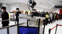 Penumpang yang tiba dengan salah satu penerbangan terakhir dari kota Wuhan China berjalan melalui stasiun pemeriksaan kesehatan di bandara Narita di prefektur Chiba, di luar Tokyo (23/1/2020). (AFP Photo/Charly Triballeau)