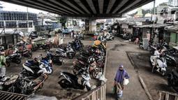 Warga saat melintas di area parkir motor warga yang juga merupakan salah satu lokasi pengungsian ketika banjir di kawasan RW 07 Rawajati, Jakarta, Selasa (22/9/2020). (merdeka.com/Iqbal S. Nugroho)