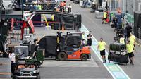 Para pekerja berkemas di pit lane setelah pembatalan Formula 1 Australia di Melbourne, Jumat (13/3/2020). Mclaren menarik diri dari balapan F1 Australia setelah salah satu stafnya positif terjangkit virus corona COVID-19. (Michael Dodge/AAP Image via AP)