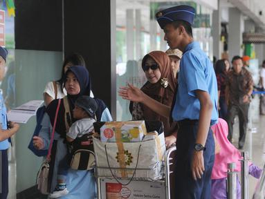 Petugas memeriksa kecocokan tiket calon penumpang pesawat di Bandara Halim Perdanakusuma Jakarta, Senin (4/7). H-2 jelang Idul Fitri 1437 H, ribuan calon penumpang diberangkatkan dari Bandara Halim Perdanakusuma. (Liputan6.com/Helmi Fithriansyah)