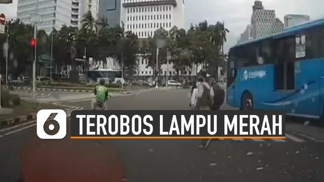 Video driver ojol terobos lampu merah diseruduk bus Transjakarta viral di media sosial.