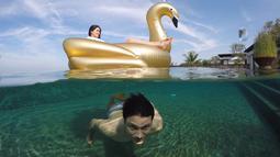 Christian Sugiono berenang di dalam air sementara Titi Kamal asyik berada di atas pelampung berbentuk bebek. Foto ini diambil saat Titi dan keluarga kecilnya mengisi liburan di Bali. (instagram.com/titi_kamall)