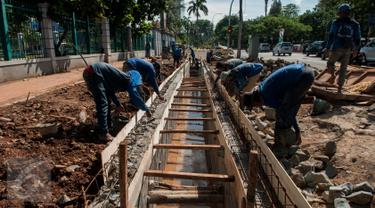 Sejumlah pekerja menyelesaikan pembuatan saluran air di Jalan Asia Afrika, Senayan, Jakarta, Rabu (5/4). Pembuatan saluran air tersebut untuk menanggulangi genangan air saat hujan turun. (Liputan6.com/Gempur M Surya)