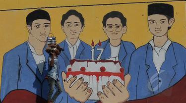 Mural bergambar empat mahasiswa Trisakti yang tewas tertembak saat melakukan aksi pada 12 Mei 1998 lalu, Jakarta, Selasa (12/5/2015). Hingga kini pelaku dan dalang peristiwa 12 Mei 1998 belum terungkap. (Liputan6.com/Johan Tallo)