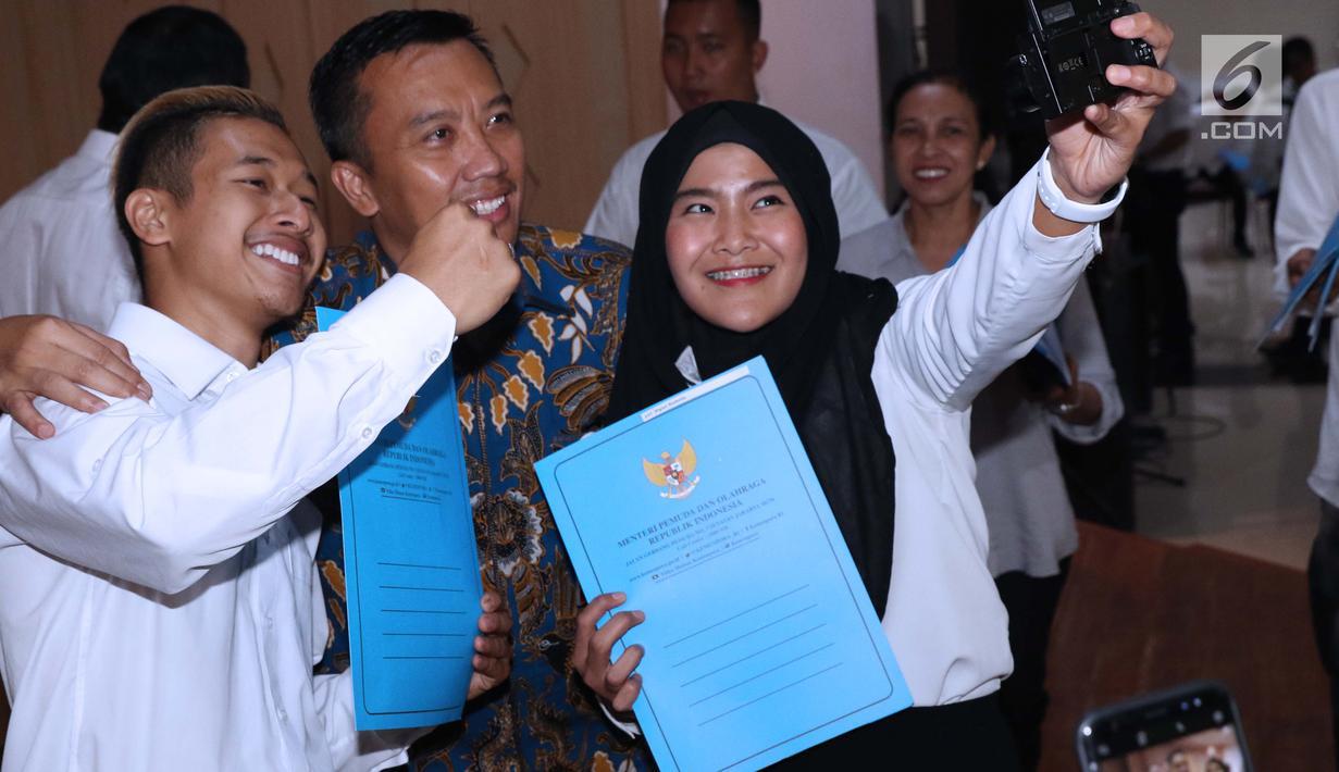 Sejumlah atlet berswafoto dengan Menpora Imam Nahrawi usai menerima SK CPNS di Wisma Kemenpora, Jakarta, Selasa (2/4). 286 atlet berprestasi menerima SK pengangkatan sebagai CPNS di lingkungan Kemenpora. (Liputan6.com/Helmi Fithriansyah)