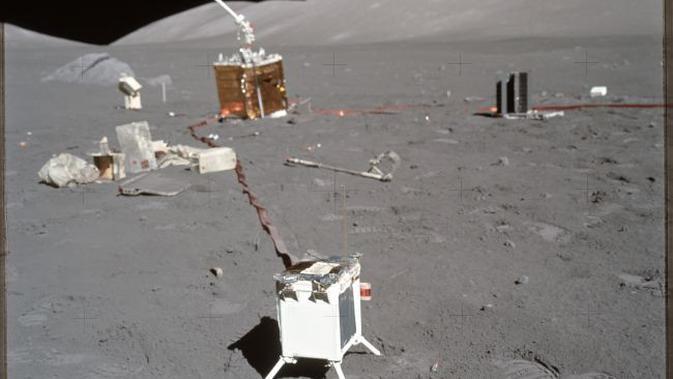 Sebuah foto yang diambil selama Apollo 17 menunjukkan percobaan sains di latar depan dan latar belakang dengan tumpukan puing-puing, termasuk pembungkus percobaan dan sampul di sebelah kiri. (NASA)