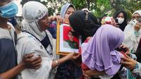 Istri prajurit TNI Gugur di Poso mencium foto suaminya itu saat pemakaman di Pekanbaru. (Liputan6.com/M Syukur)