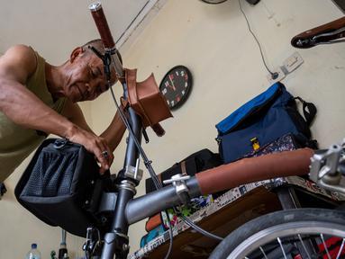 Taylor Amin Robert melakukan test-fit sebuah tas sepeda buatan tangannya di rumahnya, Jakarta (18/2/2020). Taylor yang otodidak memulai karirnya 30 tahun lalu, sekarang berspesialisasi dalam tas sepeda, dengan mayoritas klien mengendarai sepeda lipat di jalan-jalan kota. (AFP/Bay Ismoyo)
