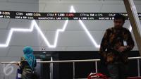 Pekerja melintas di bawah layar indeks saham gabungan di BEI, Jakarta, Selasa (4/4). Sebelumnya, Indeks harga saham gabungan (IHSG) menembus level 5.600 pada penutupan perdagangan pertama bulan ini, Senin (3/4/2017). (Liputan6.com/Angga Yuniar)