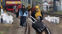 Sejumlah penumpang KRL Commuter Line terpaksa berjalan kaki menuju Stasiun Bojonggede, Bogor, Jawa Barat, Minggu (4/8/2019). Padamnya listrik di wilayah Jabodetabek mengakibatkan perjalanan KRL Commuter Line terhenti. (Liputan6.com/Helmi Fithriansyah)