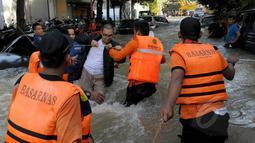 Petugas Basarnas membantu warga menyeberangi banjir di Perumahan Ciledug Indah 1, Tangerang, Selasa (10/2/2015). (Liputan6.com/Andrian M Tunay)