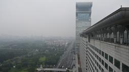 Gedung pencakar langit Pangu Plaza yang mendominasi daerah di seberang Stadion Olimpiade Bird's Nest, pusat kota Beijing, Selasa (20/7/2019). Bangunan 40 lantai hasil sitaan terkait kasus korupsi itu terjual dalam lelang online dengan harga 734 juta USD atau sekitar Rp10,5 triliun. (GREG BAKER/AFP)