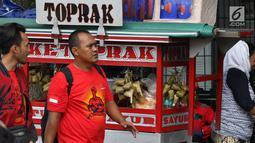 Dua pria berjalan melewati pedagang ketoprak yang menjajakan dagangannya di sisi jalan sekitar kawasan Patung Kuda Jakarta, Rabu (5/1/2019). Mereka mencoba peruntungan saat para buruh melakukan aksi perayaan Hari Buruh International atau May Day. (Liputan6.com/Helmi Fithriansyah)