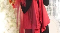 Tampil menyumbangkan suara emasnya dalam acara pernikahan rekannya, Inka Christie tampil dengan gaya pakaian hijab merah dan hitam lengkap dengan hiasan khas penyanyi rock (Liputan6.com/Instagram/@inka_christie99)