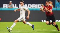 Gelandang Real Madrid, Gareth Bale menggiring bola dari kejaran bek Manchester United, Luke Shaw saat bertanding pada International Champions Cup di Miami Gardens, Fla (31/7). MU menang tipis 2-1 atas Madrid. (Jim Rassol/South Florida Sun-Sentinel via AP)