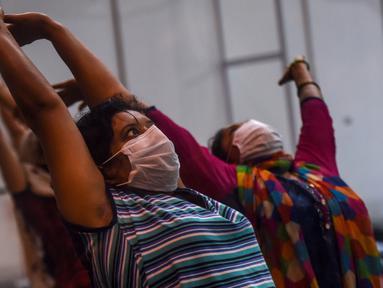 Pasien melakukan yoga di dalam bangsal di kompleks olahraga Commonwealth Games (CWG) Village yang sementara diubah menjadi pusat perawatan Covid-19 di New Delhi, India, Kamis (16/7/2020). Kasus virus corona (Covid-19) di India hampir menyentuh angka 1 juta orang.  (Money SHARMA / AFP)