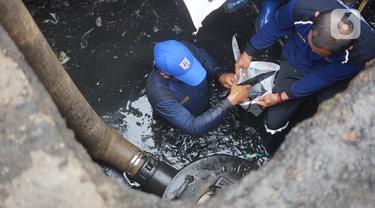 Petugas Sudin Sumber Daya Air Jakarta Timur membersihkan saluran gorong-gorong yang tertutup lumpur dan sampah di kawasan Pasar Rebo, Kamis (19/3/2020). Pembersihan untuk memperlancar sistem drainase yang tersumbat dan kerap menimbulkan genangan air di kawasan itu. (Liputan6.com/Immanuel Antonius)