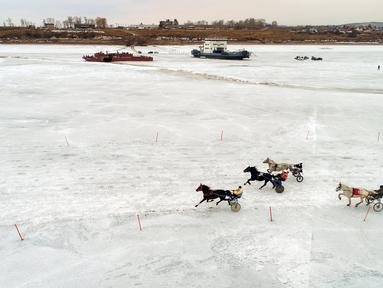 Peserta memacu troika selama bersaing dalam balapan kuda Ice Derby di Sungai Yenisei yang membeku, Krasnoyarsk, Rusia (16/3). Ice Derby merupakan kejuaraan balap kuda amatir yang berlangsung setiap akhir musim dingin. (Reuters/Ilya Naymushin)