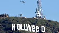 Helikopter terbang di atas tanda ikonik Hollywood yang diubah menjadi Hollyweed  di Hollywood Hills, Los Angeles, Minggu (1/1). Sebelumnya, ini telah diubah menjadi Hollyweed pada tahun 1976 oleh seorang bernama Danny Finegood. (AFP PHOTO/Gene Blevins)