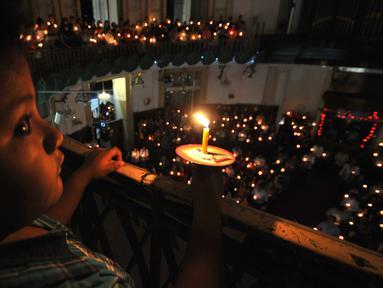 Umat Kristiani menyalakan lilin saat melaksanakan ibadah malam Natal di Gereja Protestan Indonesia Bagian Barat (GPIB) Immanuel, Jakarta, Kamis (24/12). Umat Kristiani merayakan Hari Raya Natal pada 25 Desember. (Liputan6.com/Gempur M Surya)