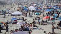 Pengunjung berkumpul di Pantai Newport selama masa pandemi covid-19 di California pada Minggu (24/5/2020). Warga Amerika Serikat mengabaikan pedoman jarak sosial dan memilih berjemur di pantai ketika angka kematian akibat virus corona di negara itu mendekati 100.000 orang. (AP/Marcio Jose Sanchez)