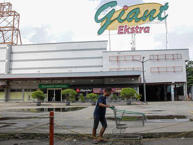 Pengunjung melintas di depan Supermarket Giant Ekstra di Kreo, Tangerang, Senin (2/8/2021). PT Hero Supermarket Tbk resmi menutup seluruh gerai Giant di Indonesia pada Minggu (1/8/2021), dan akan lebih fokus pada pengembangan gerai merek lainnya. (Liputam6.com/Faizal Fanani)