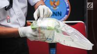 Petugas menata barang bukti 25 kilogram sabu di Kantor BNN, Jakarta, Senin (22/5). BNN mengungkap kasus peredaran Narkoba jaringan internasional yang dikendalikan terpidana mati, Togiman alias Toge dari Lapas Tanjung Gusta. (Liputan6.com/Yoppy Renato)
