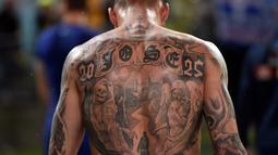 Pemain Yunani, Chose Cholevas memiliki tato unik saat berjalan keluar arena pada partai persahabatan melawan Australia di Sidney. (AFP/Saeed Khan)