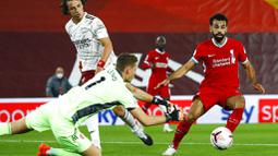 Kiper Arsenal, Bernd Leno, berusaha menghalau tendangan penyerang Liverpool, Mohamed Salah, pada laga Liga Inggris di Stadion Anfield, Senin (28/9/2020). Liverpool menang dengan skor 3-1. (Jason Cairnduff/Pool via AP)