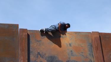 Seorang pemuda memanjat tembok besi perbatasan antara Meksiko dan Amerika Serikat di negara bagian Chihuahua, Meksiko (6/4). Mereka menyeberang secara ilegal ke Sunland Park dari Ciudad Juarez. (AFP/Herika Matinez)